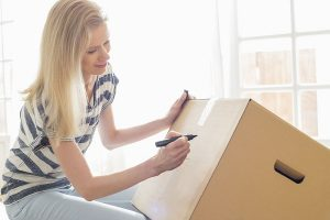 A Young Woman Makes Sure Her Moving Boxes Are Accurately Labelled